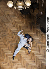 Female Tango Dancer Performing With Man On Hardwood Floor