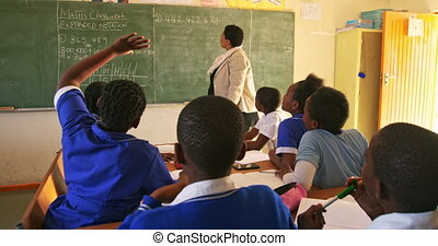 Female teacher and young pupils working in class 4k