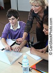 Female teacher assisting her pupils