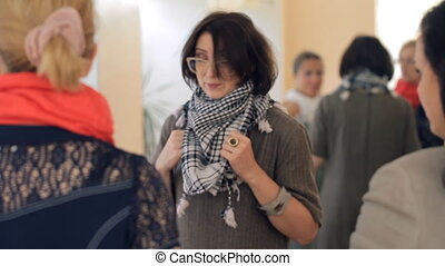 Female teacher checks as a scarf tied at three young women....