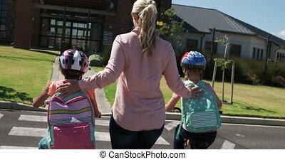 Female teacher helping kids to cross the road - Caucasian ...