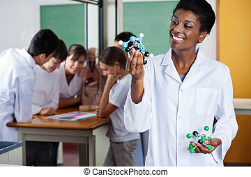 Female Teacher Looking At Molecular Structure