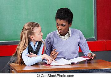 Female Teacher Looking At Schoolgirl In Classroom