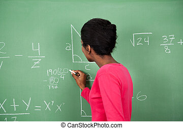 Female Teacher Solving Mathematics On Board - Side view of...