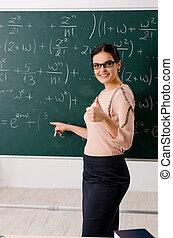 Female teacher standing in front of chalkboard