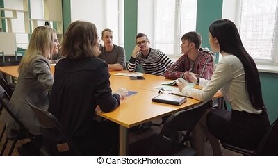 Female teacher talks with students during a lesson at university