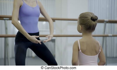 Female teacher teaches little girl in ballet school. -...