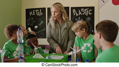 Female teacher teaching about recyclable materials in the ...
