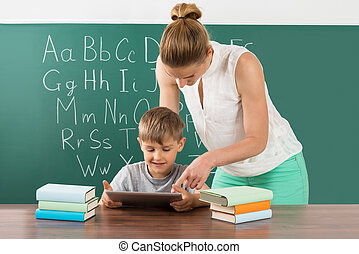 Teacher With Boy Using Digital Tablet In Classroom