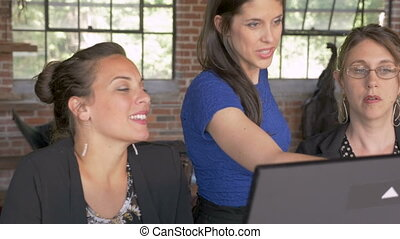 Female team leader collaborating with other women on a digital display