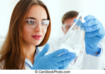 Female technician arms in protective gloves hold fluid...