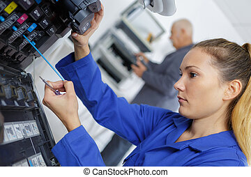 female technician checks the level of ink in office printer
