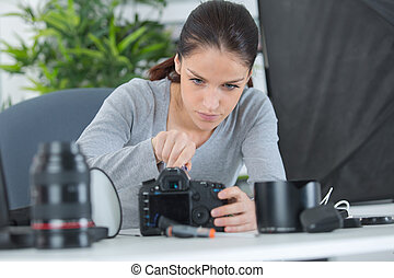female technician cleaning cameras