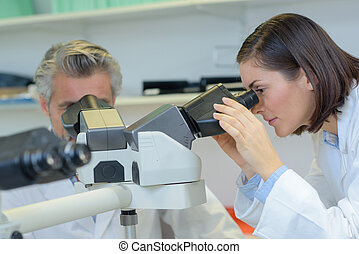 Female technician looking into microscope