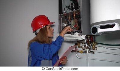 Female technician make maintenance of heating boiler in ...