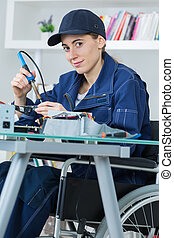 female technician on wheelchair welding an electronic circuit