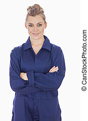 Portrait of happy young female technician with arms crossed standing against white background