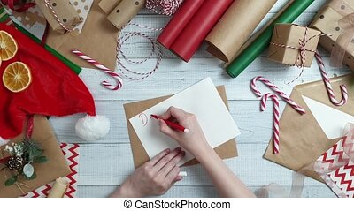 Female teen hand writing a letter to Santa on wooden table...