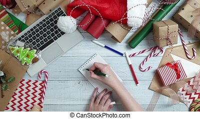 Female teen hand writing a wish list to Santa on wooden...