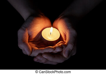 female teen hands holding burning candle