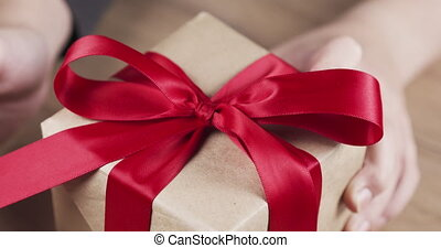 female teen hands unties the red bow on paper box