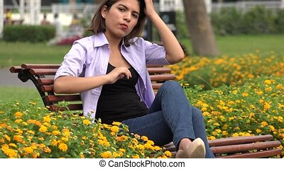 Female Teen Sitting On Park Bench