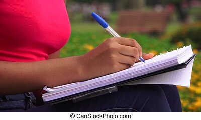Female Teen Writing In Journal Or Notebook