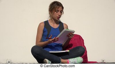 Female Teenage Student Reading And Studying