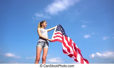 Female teenager girl holding American flag in nature - Young...