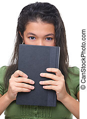 A female teenager hiding half her face behind hard cover book.