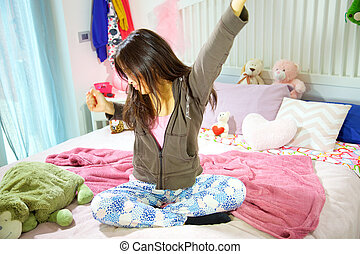 Female teenager yawning sitting in bed tired in the morning wide shot
