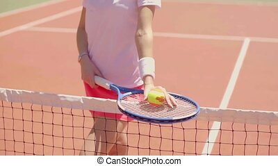 Female tennis player balancing her racket on a net