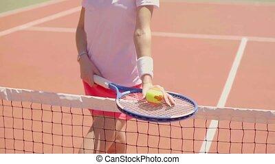 Female tennis player balancing her racket on a net