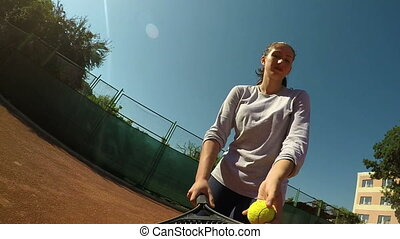 Female tennis player concentrates in serving and hits the ball