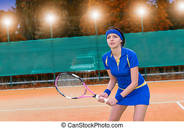 Female tennis player during the game on clay court background with lights outdoor in evening