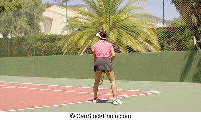 Female tennis player preparing to serve