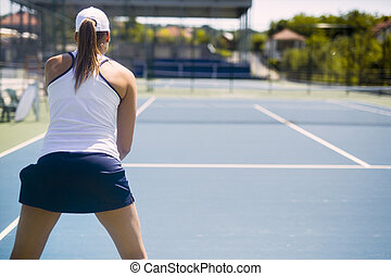 Female tennis player receiving service