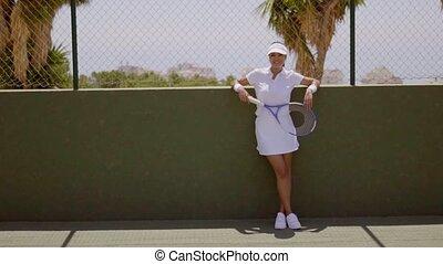 Female Tennis Player Taking a Break on Sunny Court - Full...