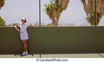 Female Tennis Player Taking a Break on Sunny Court