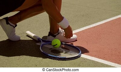 Female tennis player tying her laces on her sports shoes bending down at the edge of the all weather court with her racket alongside her close up of her hands.