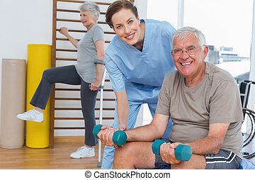 Female therapist assisting senior man with dumbbells