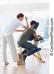 Female therapist giving back massage to man