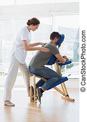 Female therapist massaging man in hospital
