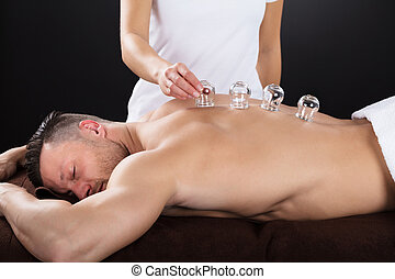 Female Therapist Placing Cups On Man's Back - Female...