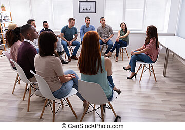 Female Therapist Speaking To Group At Therapy Section
