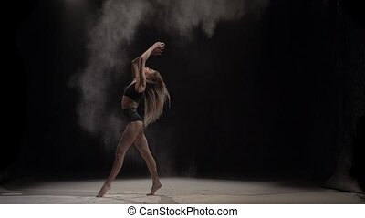 Female throwing dust particles in air at studio. Slow motion...