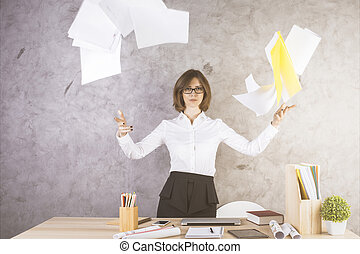 Female throwing papers - Female standing next to office desk...