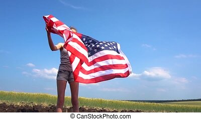 Female throws USA flag in the air in nature - Female teen...