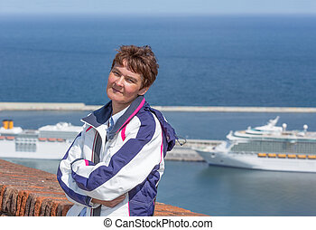 Female tourist at mountain Montjuic in Barcelona with background cruise ships