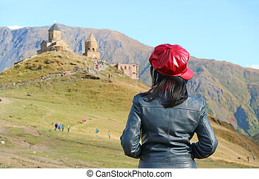 Female Tourist being Impressed by the Gergeti Trinity Church on the Hill against Kazbek Mountain, Stepantsminda, Republic of Georgia
